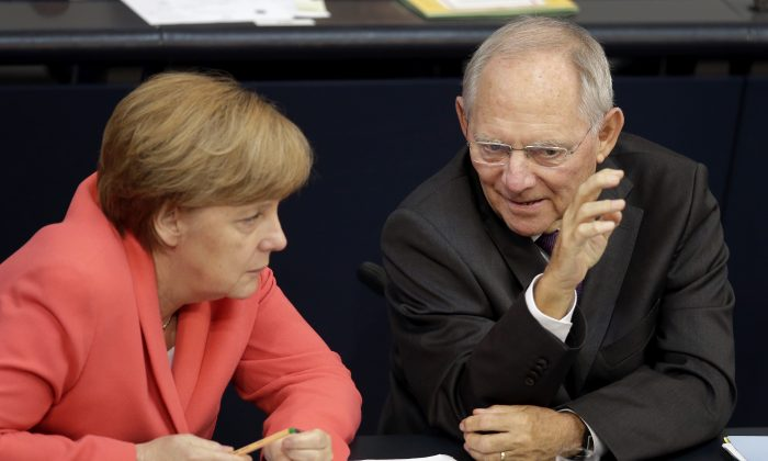German Chancellor Angela Merkel, left, and German Finance Minister Wolfgang Schaeuble, right, talk during a meeting of the German federal parliament, Bundestag, in Berlin, Germany, Friday, July 17, 2015.  (AP Photo/Michael Sohn)