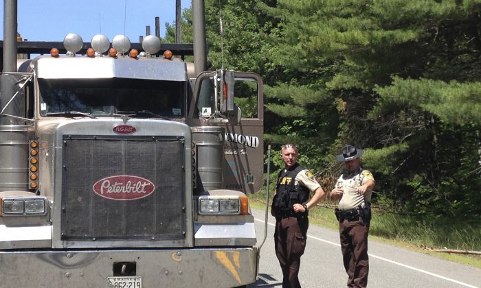 Penobscot County Sheriff deputies talk to a truck driver at checkpoint Friday, July 17, 2015, in Lee, Maine. Police were searching for a gunman in a stolen logging truck following the shootings of four people overnight in the towns of Lee, Benedicta and Silver Ridge in northern Maine.  (AP Photo/Alanna Durkin)