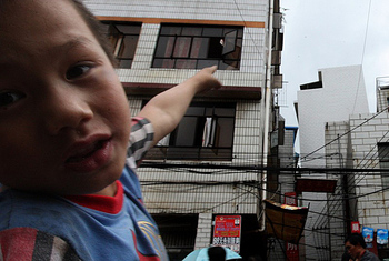 After the earthquake on August 30, a child points a obviously inclined building.   The Epoch Times (The Epoch Times)