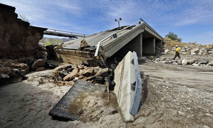 A worker walks near a washed-out bridge near the town of Desert Center, along Interstate 10 in Southern California, on Monday, July 20, 2015. (AP Photo/Nick Ut)