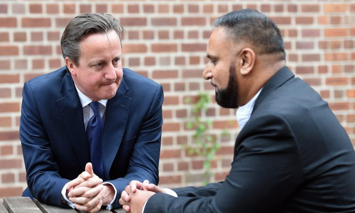 British Prime Minister David Cameron, speaks with Abdullah Rehman, a local resident whose family Cameron once stayed overnight with in 2007, in Birmingham, central England, on July 20, 2015, before delivering a speech at Ninestiles Academy. (Paul Ellis/AFP/Getty Images)