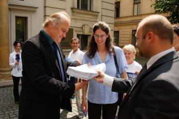 Czech Minister for Human Rights and Minorities Michael Kocab (left) receives the petitions from the Falun Gong Association representatives. (Kamil Rakyta/The Epoch Times)