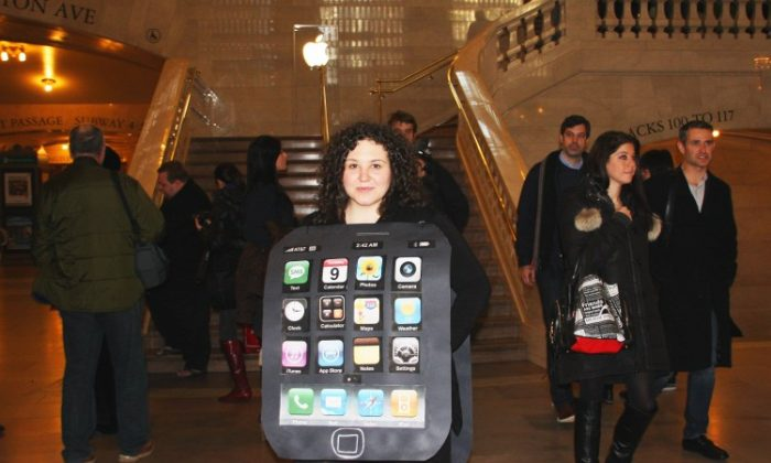 A petitioner dressed as an Apple iPhone protests outside the Apple Store in Grand Central Terminal in New York on Feb. 9. Petitioners cry fowl about the labor practices in the Chinese factories that make Apple products. (Hannah Cai/The Epoch Times)
