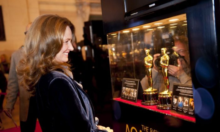 Actress Melissa Leo looks at Oscar statuettes on display at Grand Central Terminal on Wednesday. The Meet the Oscars exhibition is open from 7 a.m. to 7 p.m. Thursday, Feb. 23, through Sunday, Feb. 26 and admission is free. Fans can have photos taken with the statuettes. The awards are 13.5 inches tall and weigh 8.5 pounds. They are made in Chicago out of a metal alloy called britannia and plated with 24-karat gold. (Dai Bing/The Epoch Times)