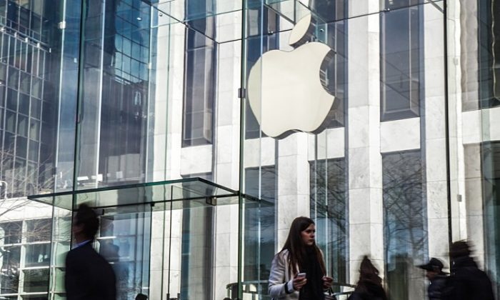 Pedestrians walk by Apple's flagship store on Fifth Avenue in Manhattan on March 27. (Benjamin Chasteen/The Epoch Times)