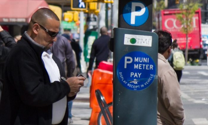 A man pays for parking at a MUNI parking meter in Midtown Manhattan on April 8. (Benjamin Chasteen/The Epoch Times)