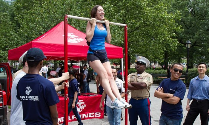 A woman does pull-ups near a recruitment tent at Marine Day at Battery Park May 25.(Benjamin Chasteen/The Epoch Times)