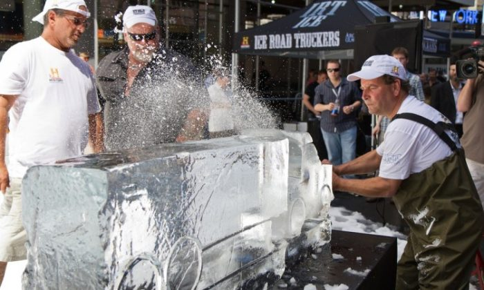"""An ice sculptor creates a truck in a block of ice using a chainsaw in 80 degree weather right in the heart of Times Square on May 31, 2012. The demonstration was a marketing campaign for History Channel's """"Ice Road Truckers."""" Star of the show, Hugh """"Polar Bear"""" Rowland, looks on. (Benjamin Chasteen/The Epoch Times)"""
