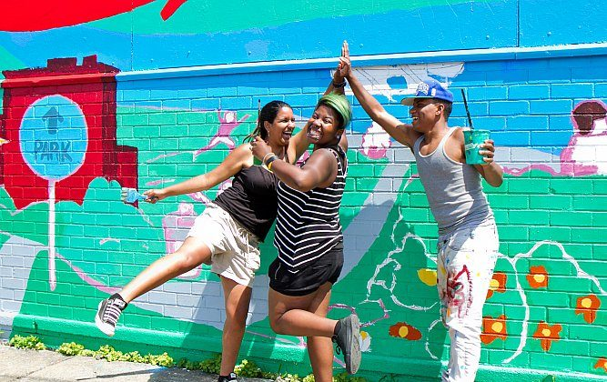 """(L-R) Ayhn Gonzalez, Tamika McLean, and Yoiky Brito, do a team """"high five"""" before they start painting the mural on the wall of a nonprofit organization, Rocking the Boat, located in Bronx, N.Y., on Aug. 13. The team has been painting the mural since July. (Benjamin Chasteen/Epoch Times)"""