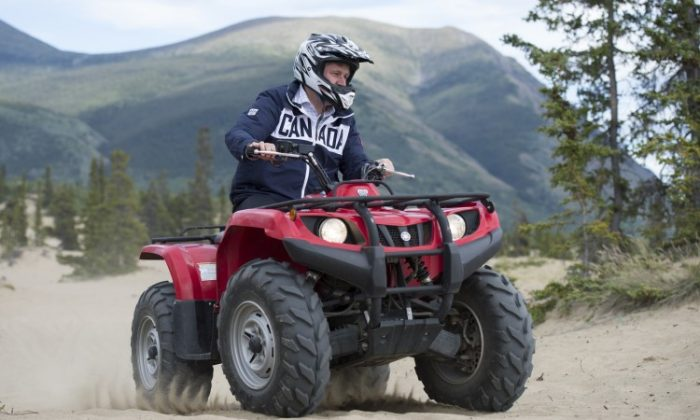 Prime Minister Stephen Harper rides an ATV in Yukon's Carcross Desert, the smallest desert in the world. Harper arrived in Yukon Aug. 20 for his seventh annual tour of the Canadian North. He is accompanied by Health Minister Leona Aglukkaq and Aboriginal Affairs and Northern Development Minister John Duncan. The trip also includes a visit to the Northwest Territories, Nunavut, and northern Manitoba. The PM is expected to make several announcements in support of the economic and social development of the North. (Jason Ransom)