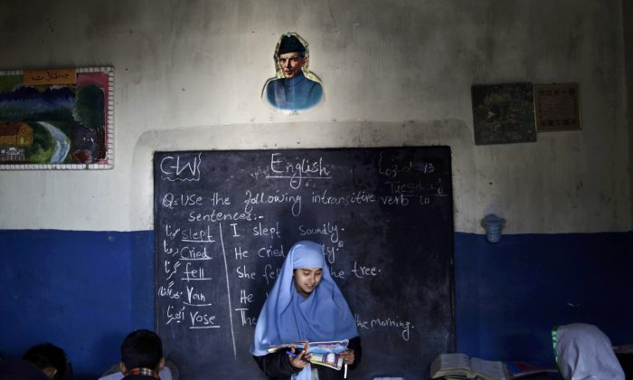 Sadia Mukhteya, 12, who was displaced with their family from Pakistan's tribal areas due to fighting between militants and the army, reads in front of the class during an English language lesson at a school in a slum on the outskirts of Islamabad, Pakistan, Thursday, Jan. 3, 2013. (AP Photo/Muhammed Muheisen)