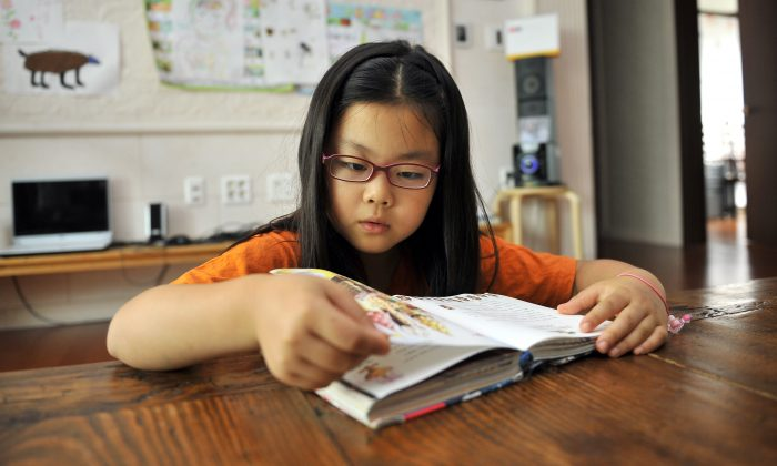 9-year-old student reads a book at home. (Jung Yeon-Je/AFP/Getty Images)