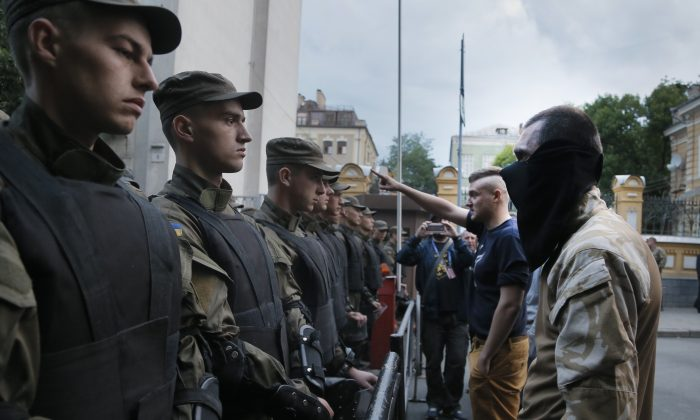 Activists from the Right Sector party confront  police who are blocking a street leading to the Ukrainian Presidential administration building in Kiev, Ukraine, on Saturday, July 11, 2015. (AP Photo/Efrem Lukatsky)
