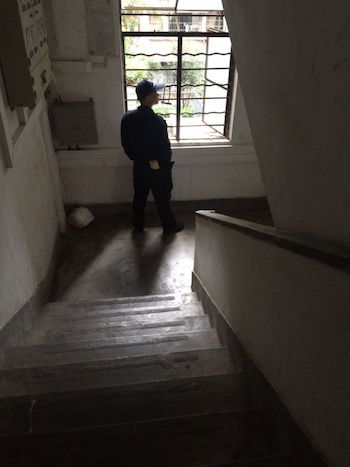 A Chinese public security officer keeps a lookout for Falun Gong practitioner Li Qiong at the stairwell of her apartment block. The photo was taken on July 8, 2015 by Ms. Li's sister. (Photo provided by Li Qiong)