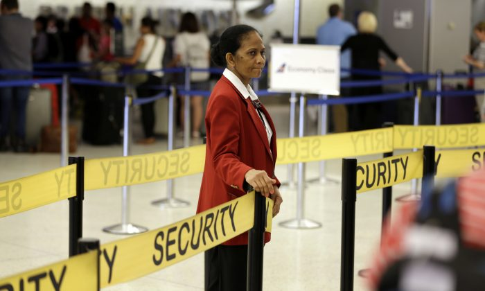 An Aviation Safeguard employee checks tickets at the JFK International Airport in a file photo. (AP Photo/Seth Wenig)