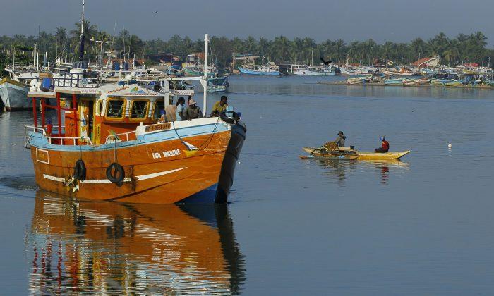 Sri Lankan fishermen stand on a fishing vessel as it leaves a fishery harbor in Negombo, Negombo, outskirts of Colombo, Sri Lanka, on Oct.15, 2014. (AP Photo/Eranga Jayawardena)