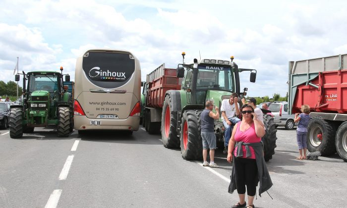 French farmers block the road leading to the famed Le Mont Saint Michel, France, Thursday July 23, 2015, hoping to get more government help to counteract cheap imports and pressure from grocery chains. (AP Photo/David Vincent)