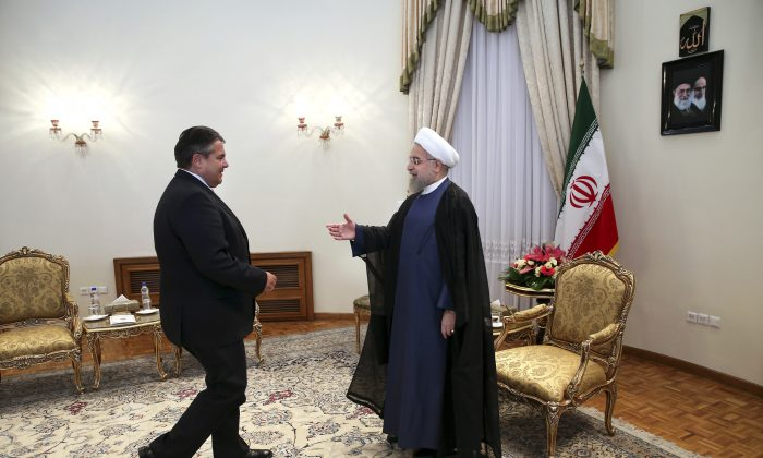 Iran's President Hassan Rouhani, right, welcomes the German Vice Chancellor and Economy Minister Sigmar Gabriel at the start of their meeting in Tehran, Iran, Monday, July 20, 2015.   (AP Photo/Ebrahim Noroozi)