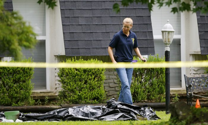 An investigator walks past a tarp covering a body in the front yard of a house in Broken Arrow, Okla., Thursday, July 23, 2015.  (AP Photo/Sue Ogrocki)