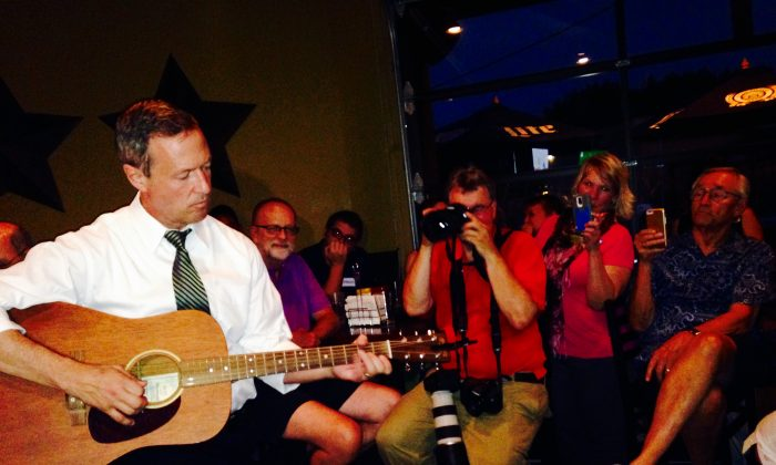 Democratic presidential hopeful Martin O'Malley plays guitar at a bar Friday, July 24, 2015, in the Beaverdale section of Des Moines, Iowa. (AP Photo/Catherine Lucey)