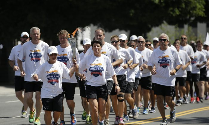 Torchbearers carrying the Flame of Hope arrive at Los Angeles City Hall, Friday, July 24, 2015, in Los Angeles. (AP Photo/Jae C. Hong)