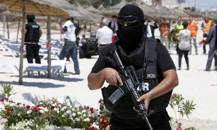 In this Monday, June 29, 2015 file photo, a hooded Tunisian police officer stands guard ahead of the visit of top security officials of Britain, France, Germany and Belgium at the scene of Friday's shooting attack in front of the Imperial Marhaba hotel in the Mediterranean resort of Sousse, Tunisa. (AP Photo/Abdeljalil Bounhar)