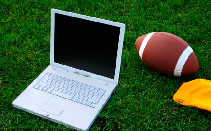 This color photo shows a closeup view of a white laptop computer, a football, and a bright-yellow penalty flag on a deep-green grassy football field in an attempt to create a fantasy-football concept image. The grassy turf fills the entire background of the image.