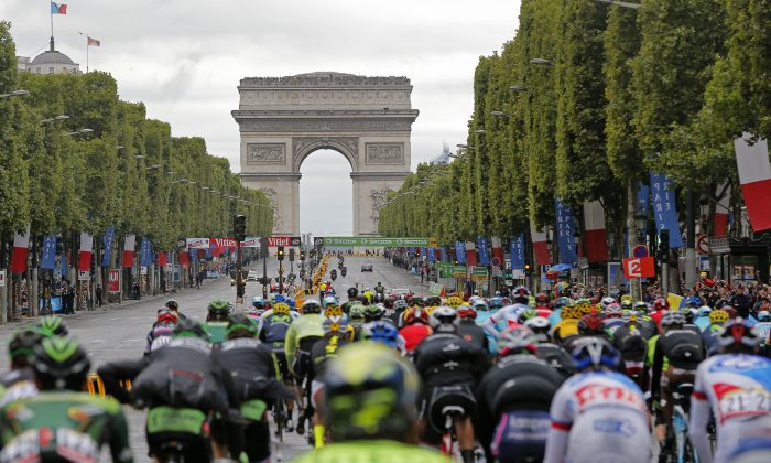 The pack rides towards the Arc de Triomphe on top of the Champs Elysees avenue during the twenty-first and last stage of the Tour de France cycling race over 109.5 kilometers (68 miles) with start in Sevres and finish in Paris, France, Sunday, July 26, 2015. (AP Photo/Christophe Ena)