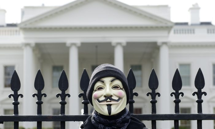 A demonstrator, including supporters of the group Anonymous, poses during a march in protest against corrupt governments and corporations in front of the White House in Washington, DC, November 5, 2013 (SAUL LOEB/AFP/Getty Images)