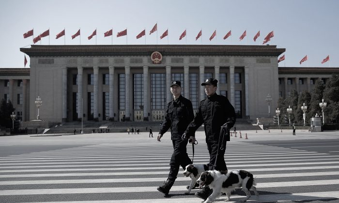 Two policeman leads police dogs guarding in front of the Great Hall of the People before the closing ceremony of the Chinese People's Political Consultative Conference on Mar. 13, 2015 in Beijing, China. (Lintao Zhang/Getty Images)