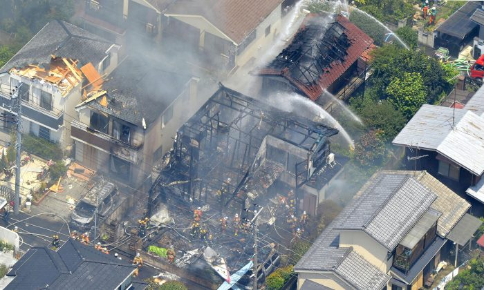 Firefighters investigate the site of a plane crash in the suburbs of Tokyo, Sunday, July 26, 2015.  (Kyodo News via AP)