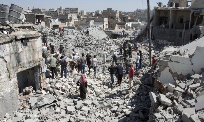 Syrians stand on the rubble of buildings after a missile fired by Syrian government forces hit a residential area in the Maghayir district in the old quarter of the northern Syrian city of Aleppo on July 21, 2015.   (KARAM AL-MASRI/AFP/Getty Images)