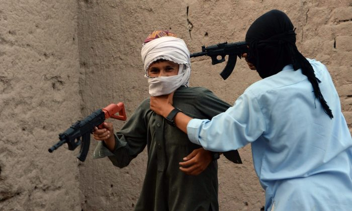 In this photograph taken on July 18, 2015, Afghan children play with plastic guns as they celebrate the second day of Eid al-Fitr which marks the end of the holy fasting month of Ramadan, on the outskirts of Jalalabad city in eastern Nangarhar province. Afghanistan banned the sale of imitation Kalashnikovs and other toy guns July 21 after they caused injuries to more than 100 people during Eid celebrations, seeking to curb a culture of violence among children. AFP PHOTO/ Noorullah Shirzada (Photo credit should read Noorullah Shirzada/AFP/Getty Images)