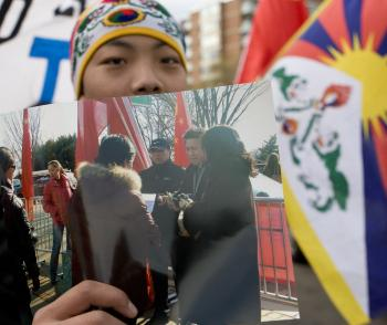A Tibetan activist holds up the photo of the money exchange. (Lisa Fan/The Epoch Times )