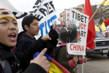 Tibetans hold up the photo and chant 'Shame! You were paid!'  (Lisa Fan/The Epoch Times )