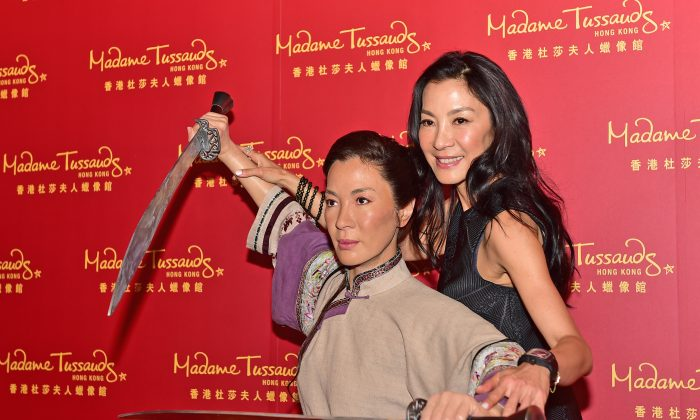Actress Michelle Yeoh poses with her Madam Tussauds, Kung Fu wax figure at its unveiling to the public in Hong Kong on July 27, 2015. (Bill Cox/Epoch Times)