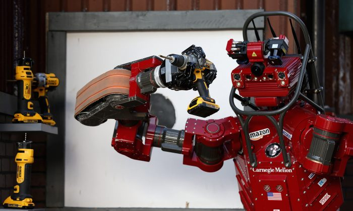 Robot uses a hand-held power tool during the cutting task of the Defense Advanced Research Projects Agency (DARPA) Robotics Challenge at the Fairplex in Pomona, Calif., on June 6, 2015. (Chip Somodevilla/Getty Images)