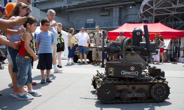 An autonomous weapon military robot preforms demonstrations for spectators at the Memorial Service on the Intrepid on May 28, 2012. (Benjamin Chasteen/Epoch Times)