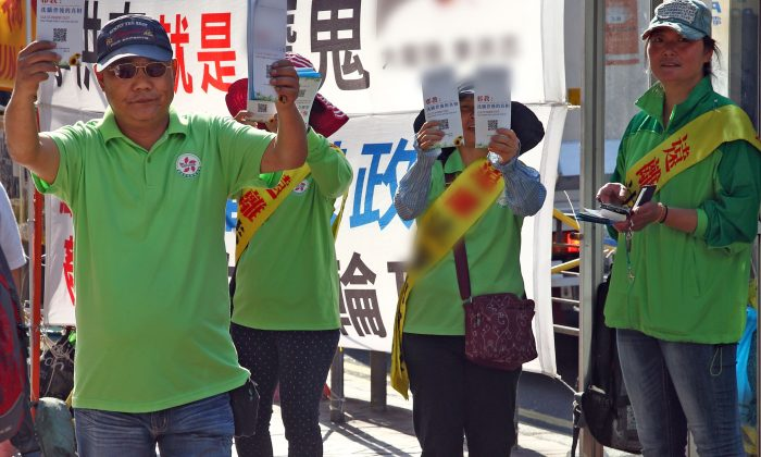 CCP supported group Hong Kong Youth Care Association (HKYCA) set information booths next to Falun Gong's and use their own banners, loudspeakers and flyers to castigate and mock Falun Gong. In the photo, the HKYCA members in green are holding slanderous flyers at Mong Kok on April 16, 2015. (Epoch Times)