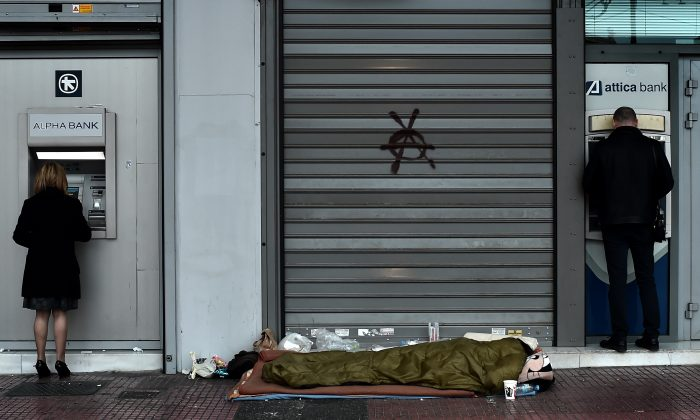 A homeless man sleeps outside a bank as people withdraw cash from ATMs in central Athens on March 13, 2015. (Aris Messinis/AFP/Getty Images)