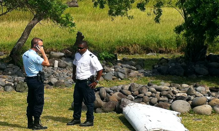 A policeman and a gendarme stand next to a piece of debris from an unidentified aircraft found in the coastal area of Saint-Andre de la Reunion, in the east of the French Indian Ocean island of La Reunion, on July 29, 2015. (Yannick Pitou/AFP/Getty Images)