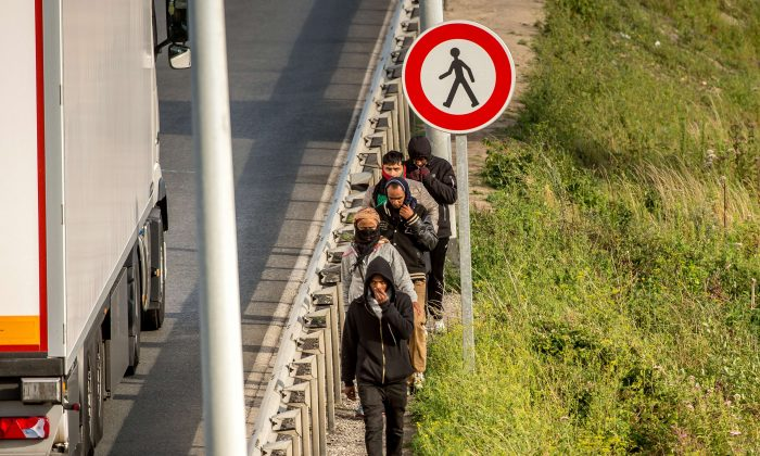 Migrants walk alongside vehicles on the route leading to the Eurotunnel in Coquelles on July 29, 2015.  Migrants walk alongside vehicles on the route leading to the Eurotunnel in Coquelles on July 29, 2015.  (Philippe Huguen/AFP/Getty Images)