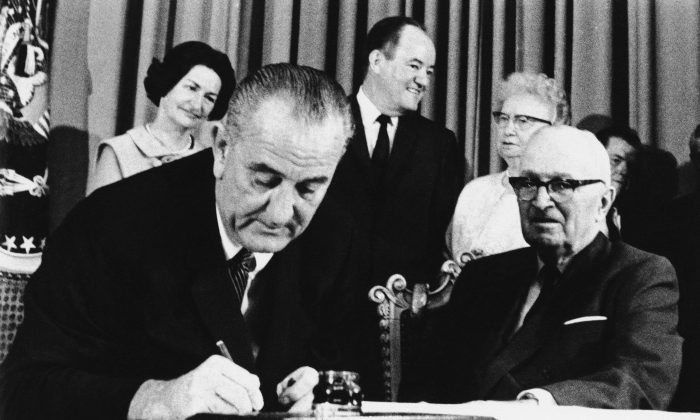FILE - In this July 30, 1965 file photo, President Lyndon Johnson signs the Medicare Bill into law while former President Harry S. Truman (R) observes during a ceremony at the Truman Library in Independence, Mo. (AP Photo)
