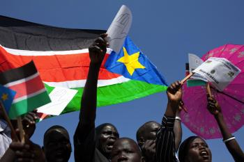 Sudanese supporters of secession wave regional flags and pro-separation placards upon the arrival of Sudan's President Omar al-Bashir at Juba airport on Jan. 4. Bashir told them in a speech in the southern capital that he would celebrate the result of thi (Yasuyoshi Chiba/AFP/Getty Images)