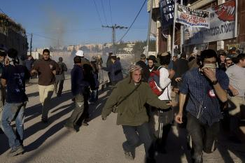 Israeli settlers flee from teargas thrown by the police after clashes erupted near a disputed house in Hebron.  (Menahem Kahana/AFP/Getty Images)