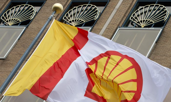 FILE - In this Monday, April 7, 2014 file photo, a flag bearing the company logo of Royal Dutch Shell, flies outside the head office in The Hague, Netherlands.  (AP Photo/Peter Dejong, File)
