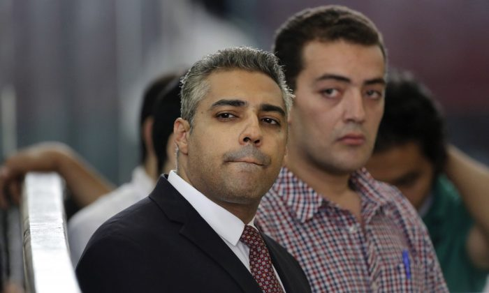 Canadian Al-Jazeera English journalist Mohammed Fahmy, left, and his Egyptian colleague Baher Mohammed listen in a courtroom in Tora prison in Cairo, Egypt on Thursday, June 4. (AP Photo/Amr Nabil)
