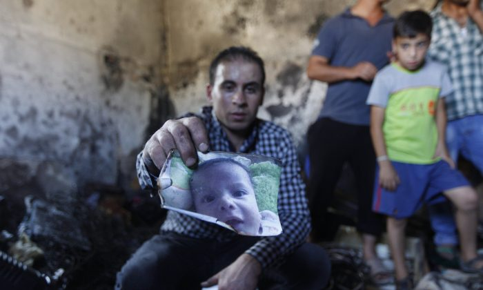 A relative holds up a photo of a one-and-a-half year old boy, Ali Dawabsheh, in a house that had been torched in a suspected attack by Jewish settlers in Duma village near the West Bank city of Nablus, Friday, July 31, 2015. (AP Photo/Majdi Mohammed)