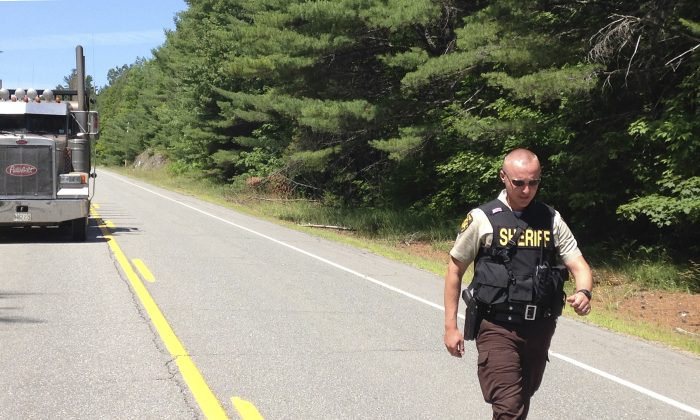 A Penobscot County Sheriff deputy walks along a road at a checkpoint Friday, July 17, 2015, in Lee, Maine.  (AP Photo/Alanna Durkin)