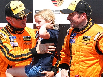 Joe Foster shares the podium with his daughter and with co-driver Scott Maxwell. (James Fish/The Epoch Times)